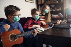 Geschwister musizieren mit Mundschutz
